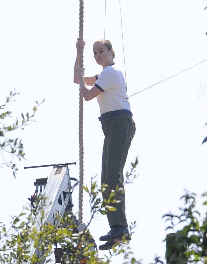 Brie Larson hangs from a rope while filming the 2019 American superhero film Captain Marvel
