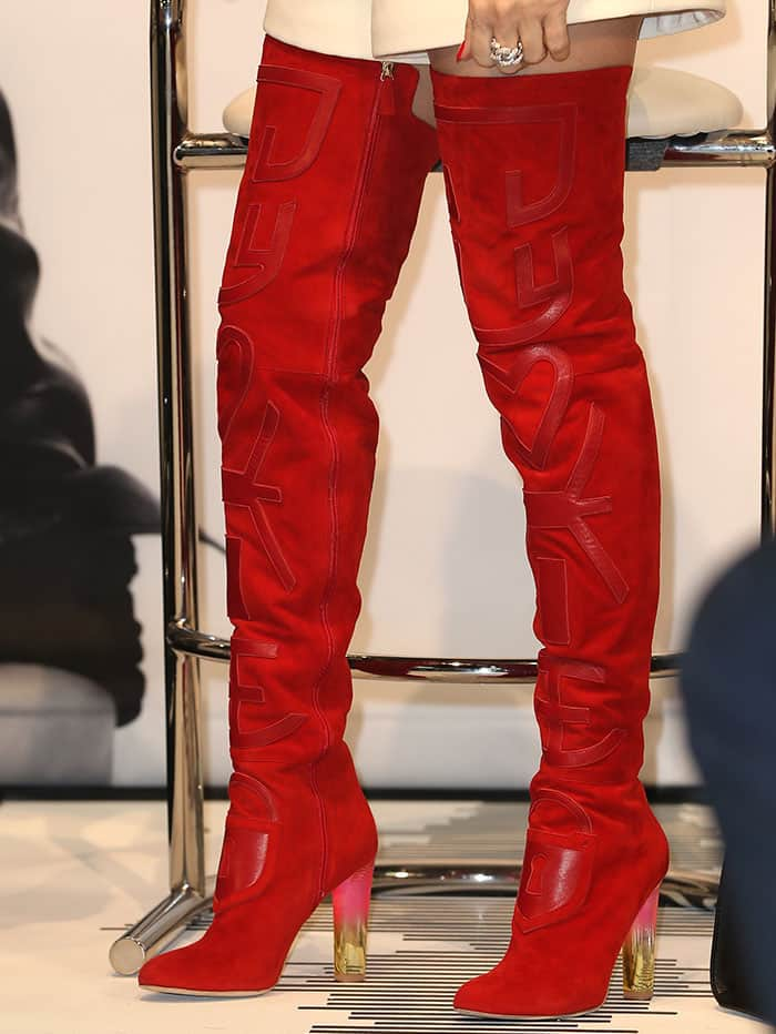 Celine Dion teamed her getup with a sexy pair of red suede thigh-high boots
