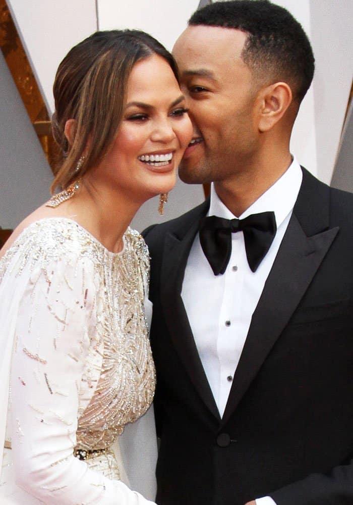 Chrissy's husband John whispers sweet nothings into her ear