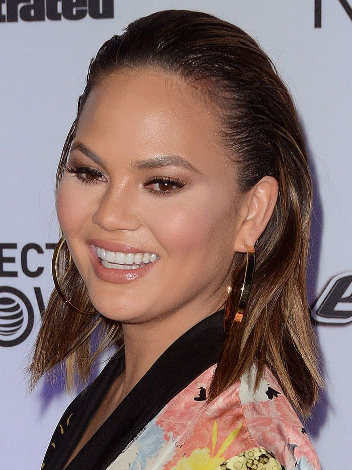 Chrissy Teigen matched her just-got-out-of-the-shower look with gold hoop earrings and wet slicked-back hair