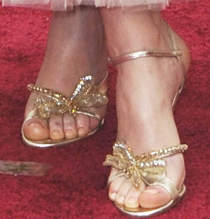 Felicity wears the gorgeous Christian Louboutin Bat Bat sandals in gold