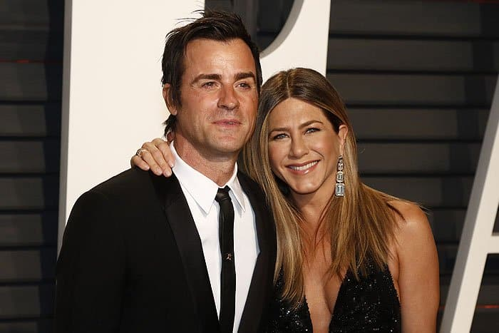 Jennifer Aniston showing off her $10.7-million Lorraine Schwartz diamond drop earrings as she poses together with husband Justin Theroux at the 2017 Vanity Fair Oscar Party