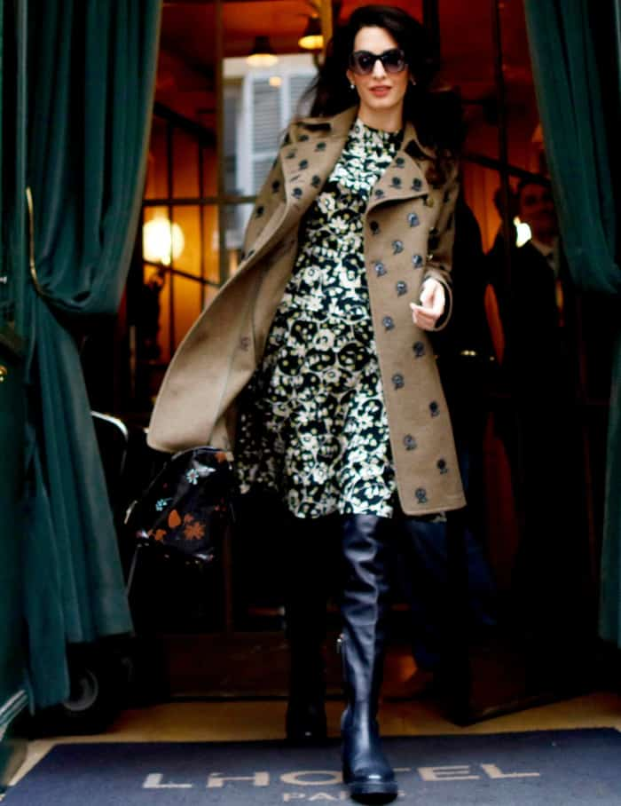 Amal Clooney wearing a monochromatic floral dress, a patterned trench coat, and over-the-knee boots in Paris
