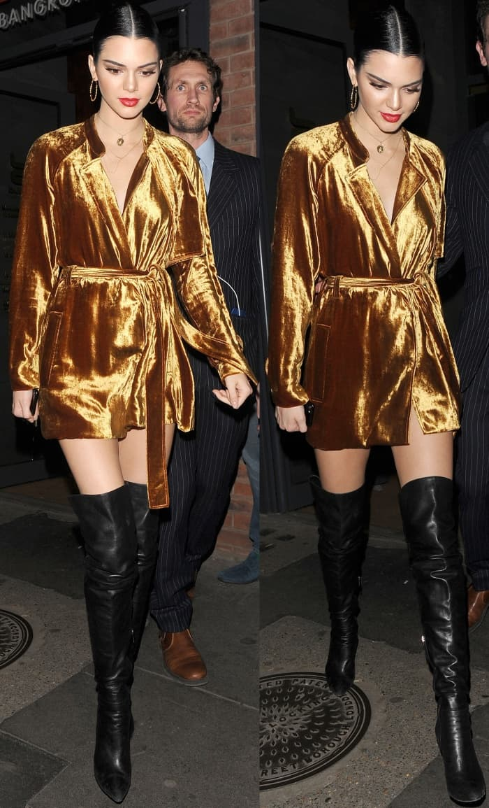 Kendall Jenner wearing a gold A.L.C. velvet wrap coat dress and black leather over-the-knee boots