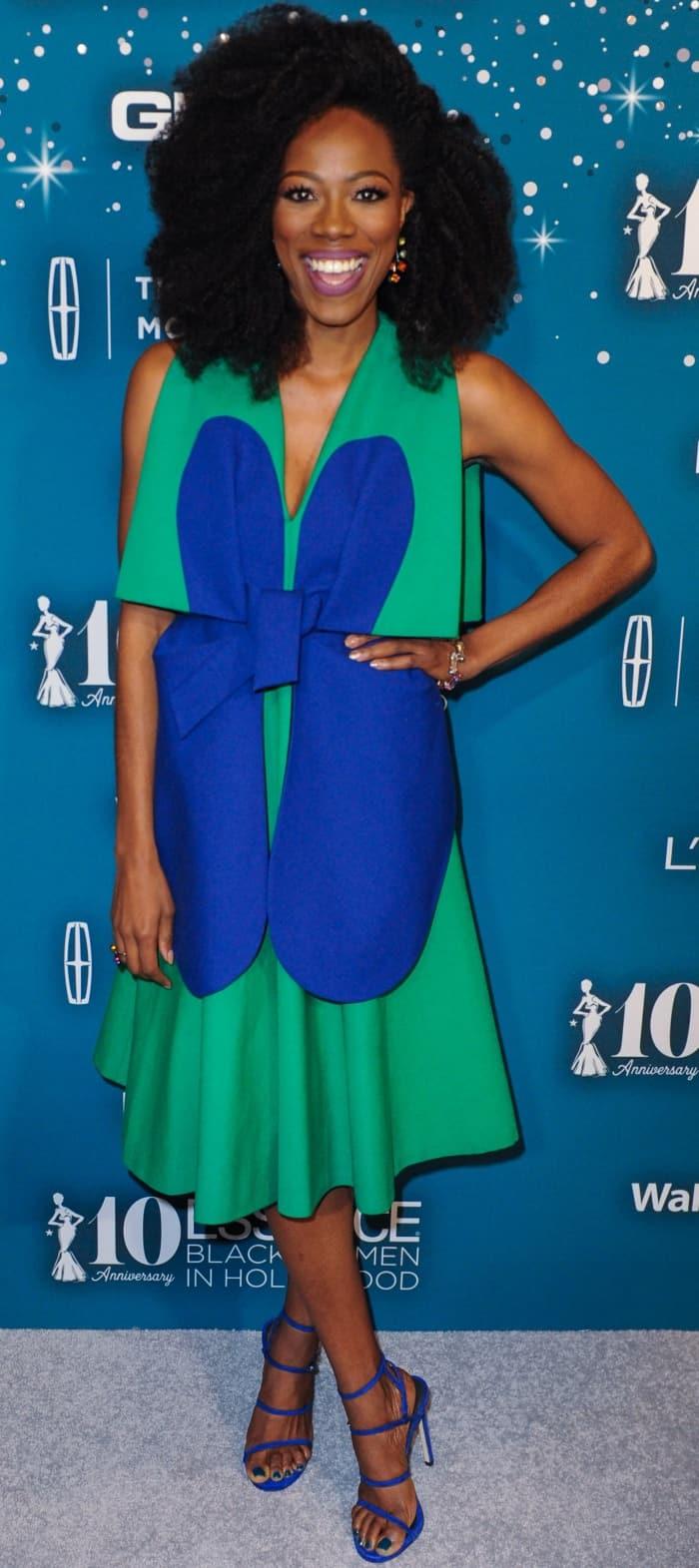 Yvonne Orji wearing a blue and green Delpozo dress and electric blue Stuart Weitzman sandals