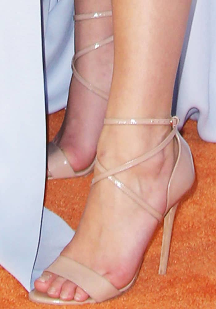 The dancer steps on the orange carpet in a pair of Brian Atwood Tamara sandals