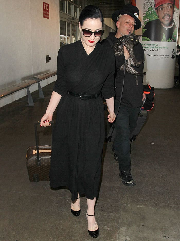 Dita Von Teese, her cat, Aleister, and a male companion making their way through LAX
