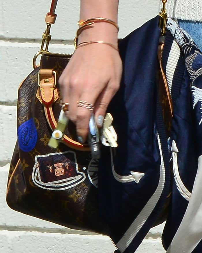 Hilary puts her essentials in the Louis Vuitton Speedy Bandouliere 30 World Tour tote