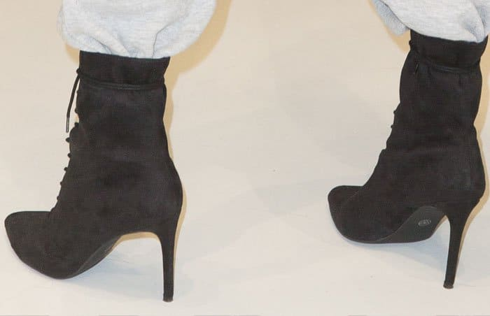 The model wears one of her ankle boots from the LonDunn + Missguided line