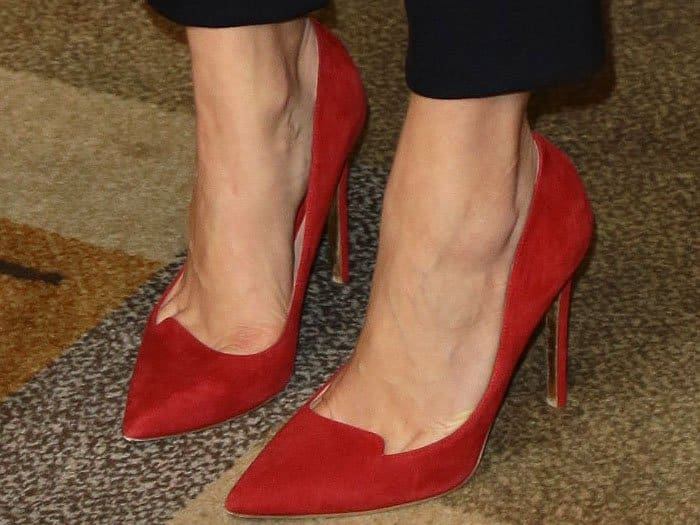 Red suede pumps with vamp notches on Lauren Cohan.