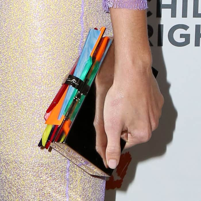 "Detail of Mandy Moore's Edie Parker ""Wolf Shard Lock"" clutch in rainbow acrylic and silver metal."