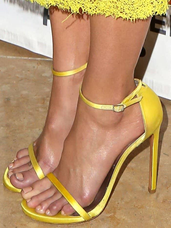 "Closeup of the Stuart Weitzman ""Nudist"" sandals in yellow satin on Mandy Moore."