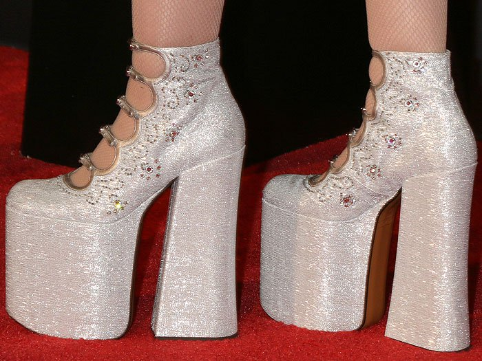 Noah Cyrus's feet in sequin-embroidered, silver sky-high platform pumps
