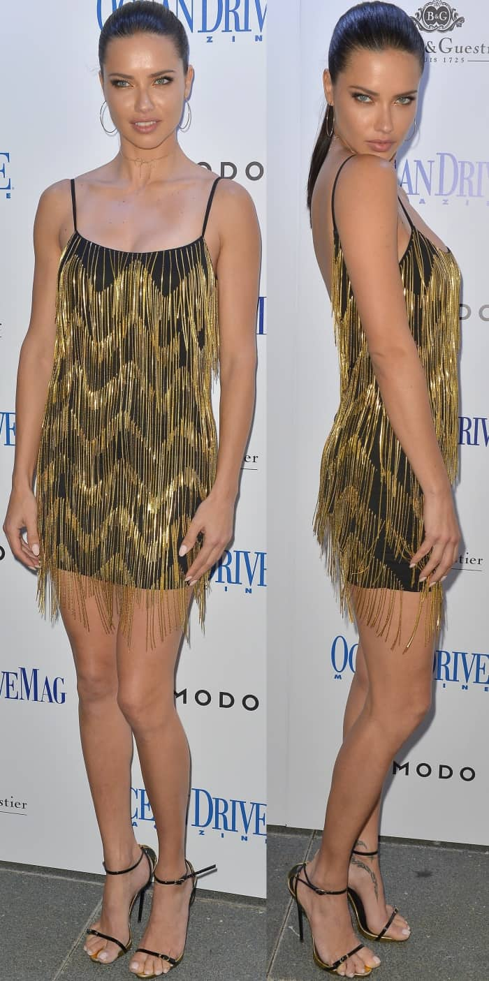 Adriana Lima wearing a black and gold cocktail dress from Misha Collection and black and gold leather sandals from Giuseppe Zanotti