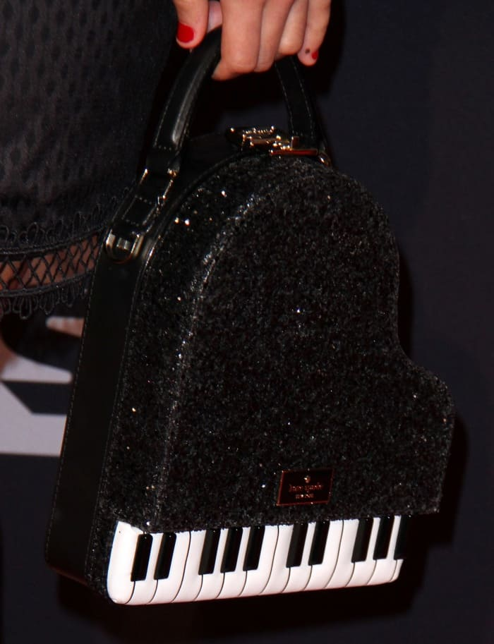 Asia Monet Ray carrying a black piano bag from Kate Spade