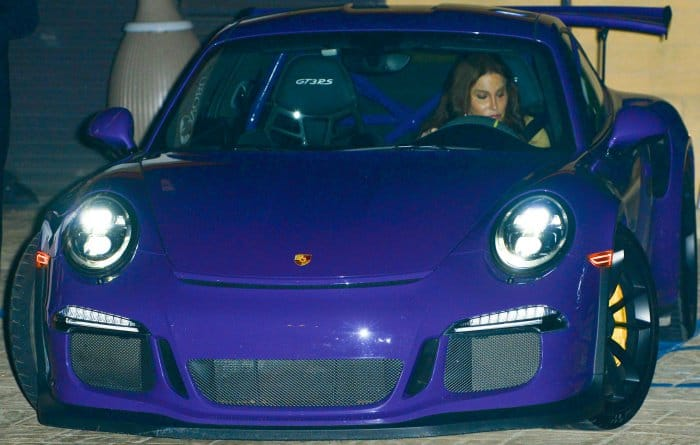 Caitlyn Jenner wearing a tan jacket, a red midi dress, and tan suede heels at Nobu restaurant in Malibu