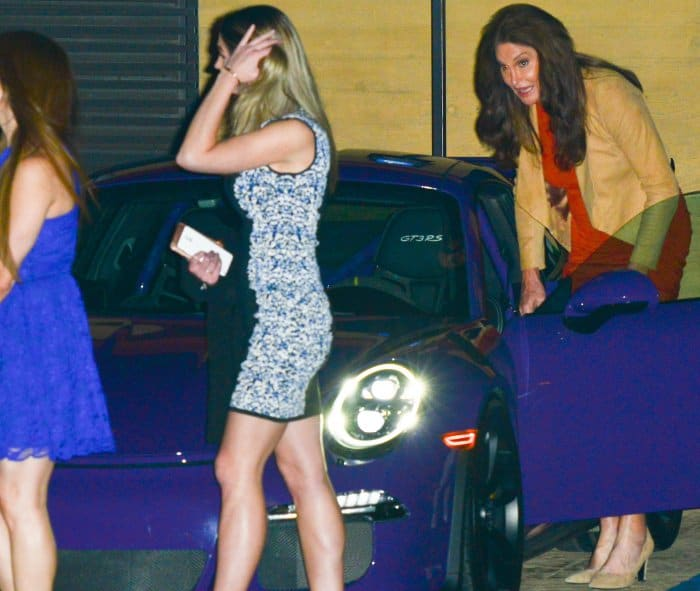 Caitlyn Jenner wearing a tan jacket, a red midi dress, and tan suede pumps at Nobu restaurant in Malibu
