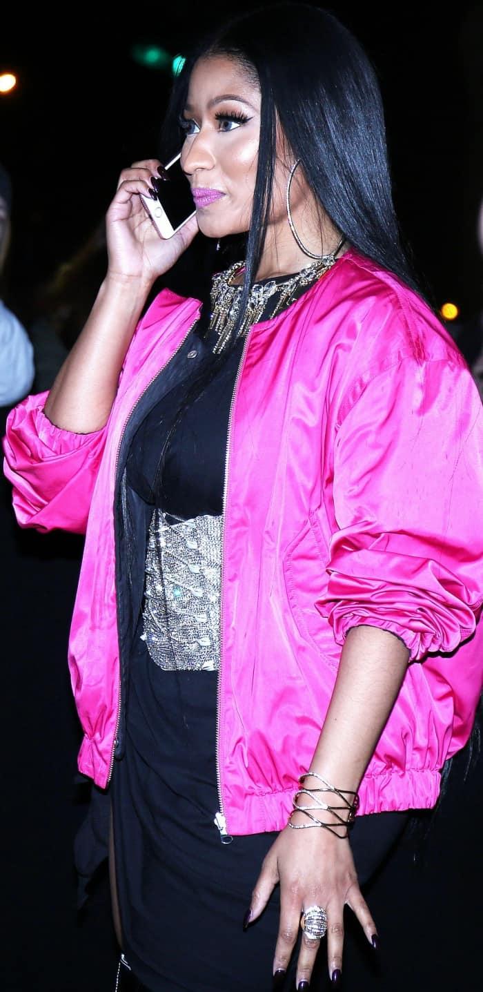 Nicki Minaj wearing a black dress, a silver corset, a hot pink bomber jacket, and Balenciaga thigh-high boots