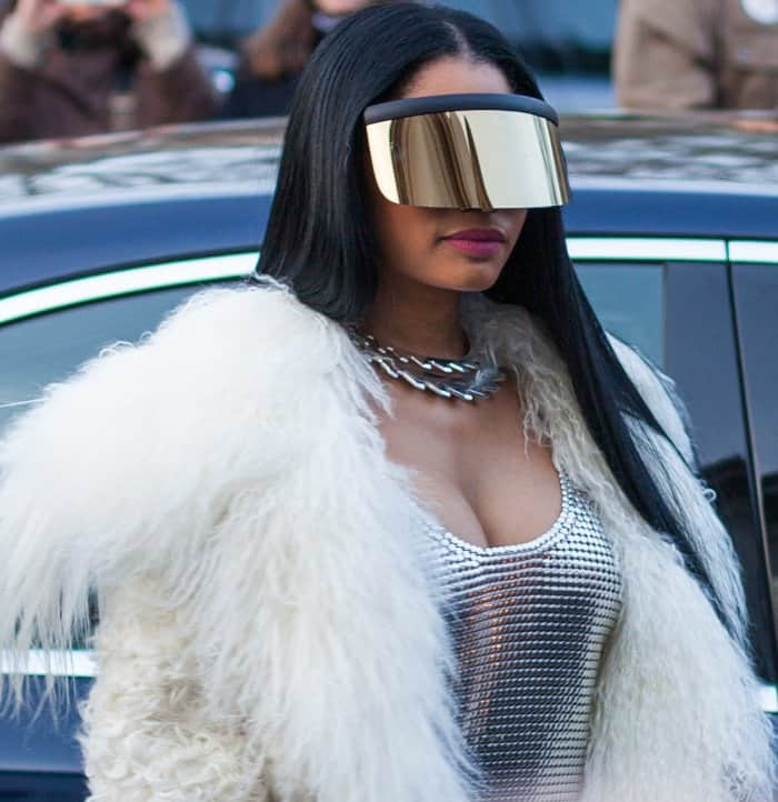 Nicki Minaj wearing a Paco Robanne chainmail dress, Monse fur coat, Mykita x Bernhard Willhelm visor, and Balmain thigh-high boots