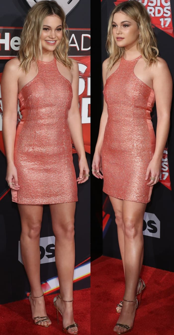 Olivia Holt wearing a salmon Kaufmanfranco dress and gold ankle-strap sandals at the 2017 iHeartRadio Music Awards