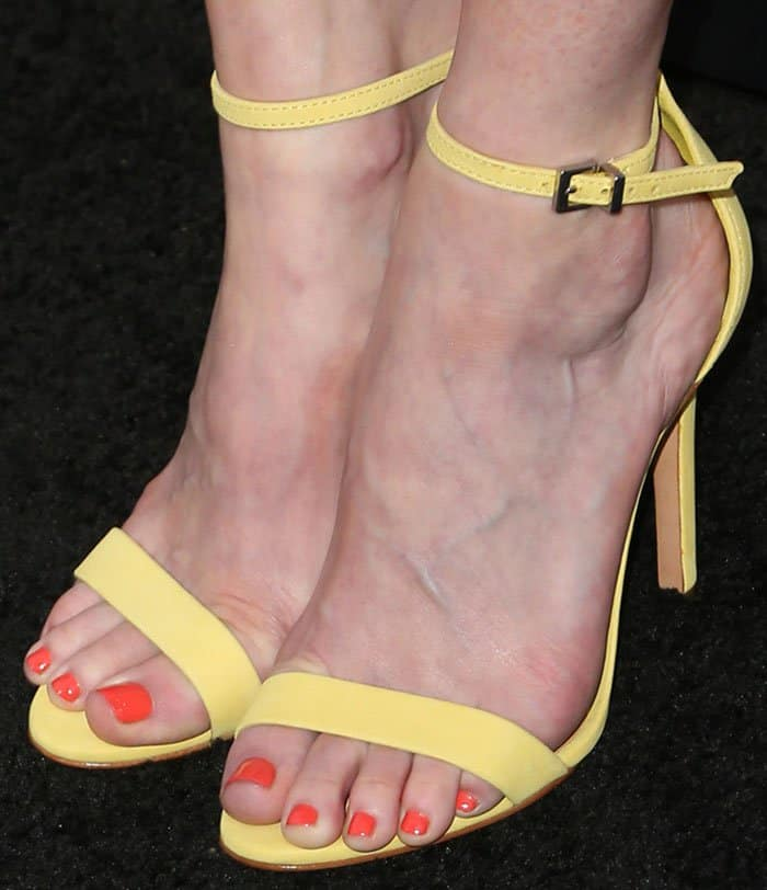 Alexis shows off her bright orange pedicure in yellow heels
