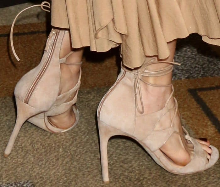 "The actress wears a youthful pair of Stuart Weitzman ""Legwrap"" sandal in nude suede"