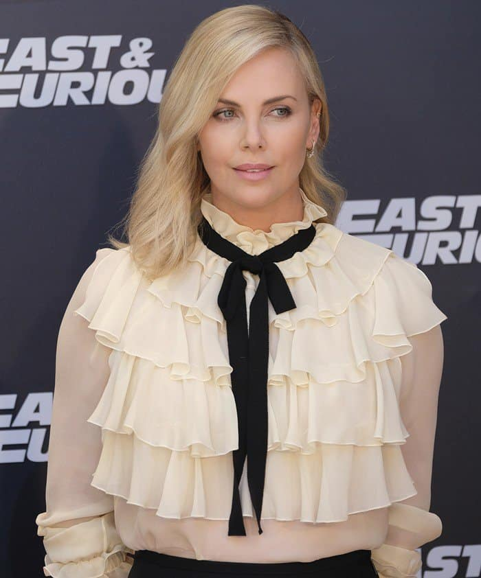Charlize Theron wearing a Gucci flounce long sleeve shirt