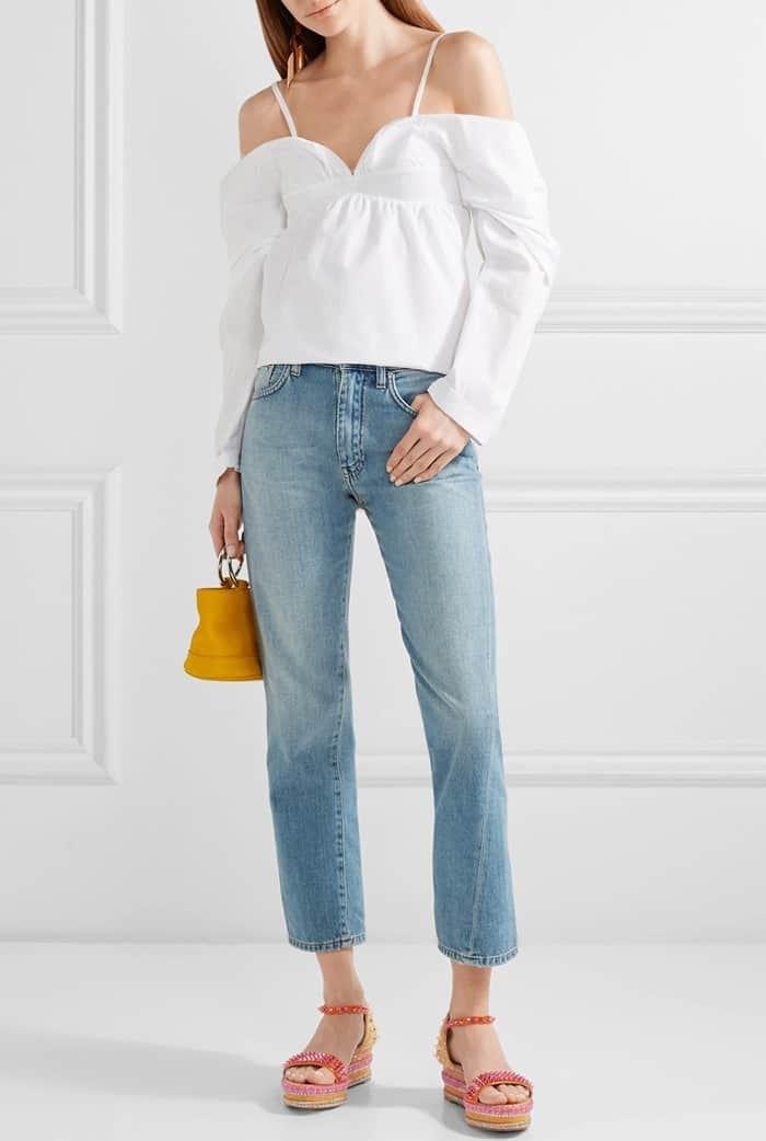 Model wearing the spiked 'Madmonica' wedge espadrille sandals with an off-the-shoulder cotton-poplin top from J.W.Anderson and cropped mid-rise slim-leg jeans from Totême's 'Original' collection