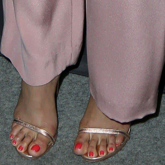 Freida Pinto showing off her feet in metallic Stuart Weitzman sandals