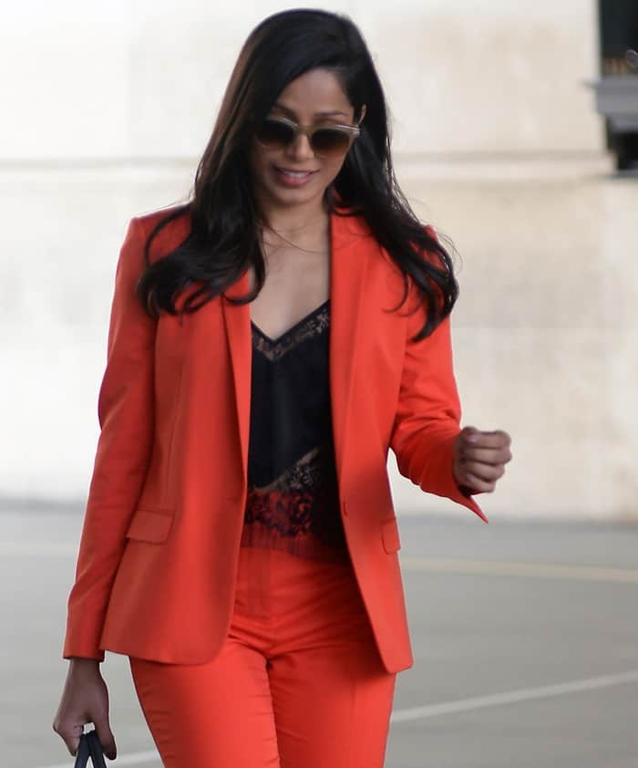 Freida Pinto wearing a red blazer and pants by Topshop styled with a black silk and lace top by Michelle Mason