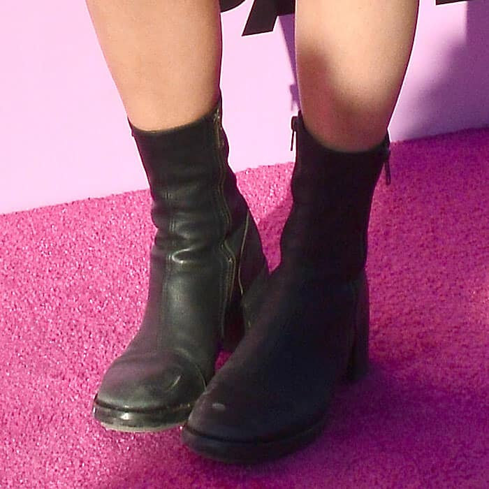Closeup of Kylie Jenner's beat-up black leather boots with scuffed toes, chunky heels, and side zippers.