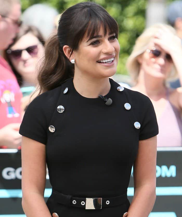 Lea Michele's black dress features metallic silver buttons and a plated belt