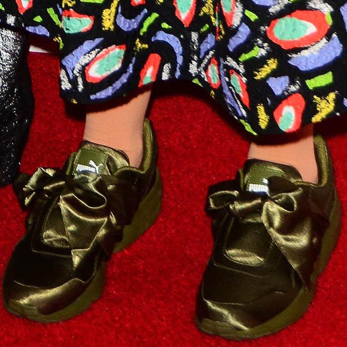 Closeups of the olive green Fenty Puma by Rihanna bow sneakers on Lena Dunham.