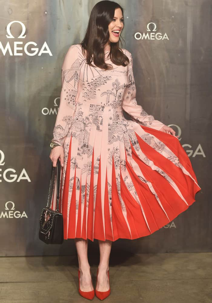 The cheerful actress plays with her beautiful pleated skirt