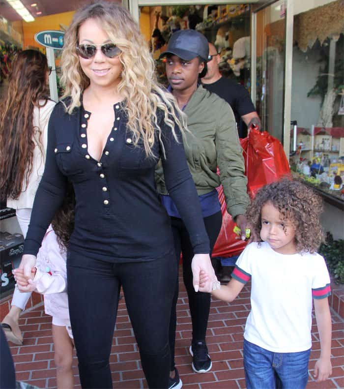 Mariah walks out of Tom's Toys with her two tikes in hand