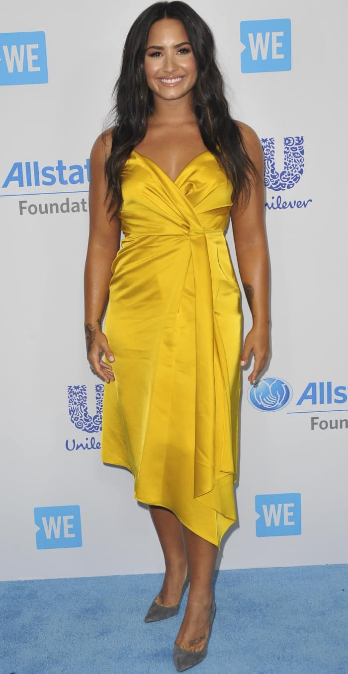 Demi Lovato in a vibrant yellow faux-wrap midi dress from Victoria Beckham
