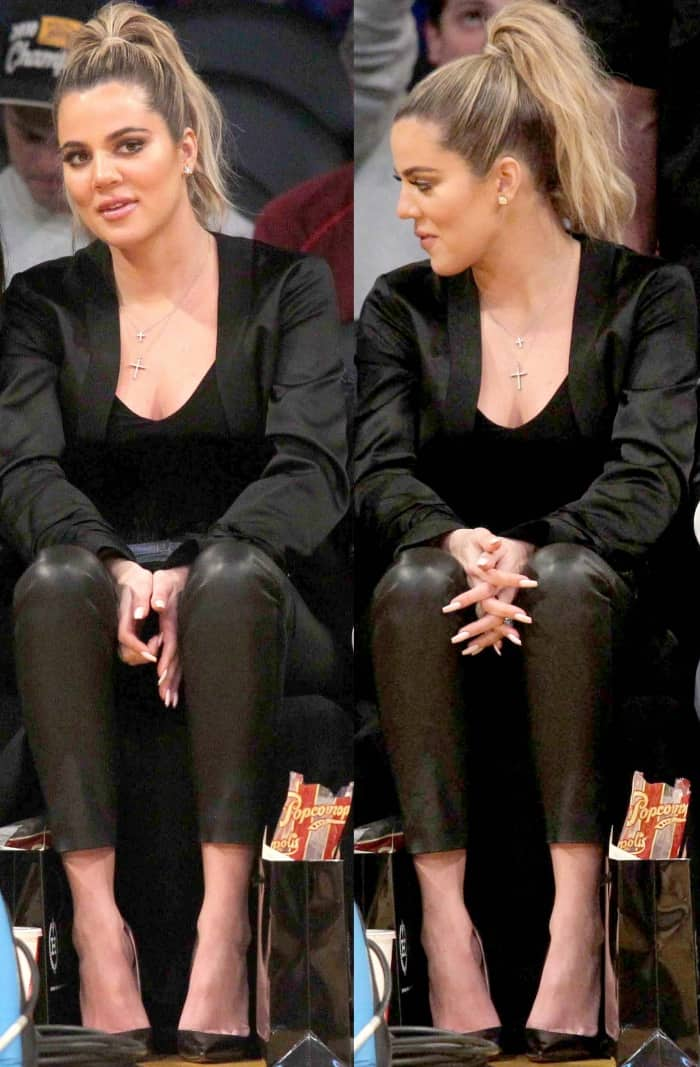 Khloe Kardashian wearing a black jacket, a black low-cut top, black leather leggings, and black pointy-toe pumps at the Lakers vs. Cavaliers basketball game