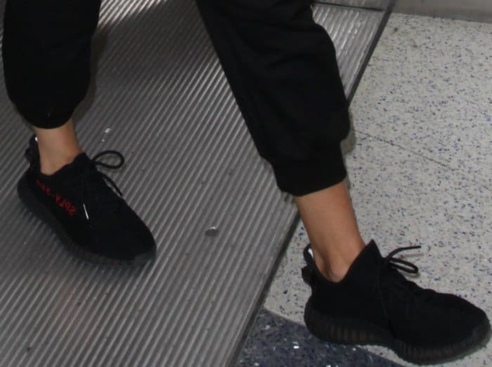 Khloe Kardashian wearing an all-black outfit styled with Yeezy Boost 350 V2 Sneakers at LAX