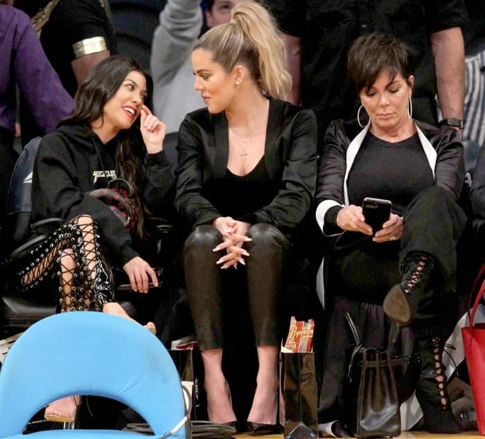 Kourtney Kardashian wearing Yeezy sandals, Khloe Kardashian wearing black pointy-toe pumps, and Kris Jenner wearing black lace-up booties at Lakers vs. Cavaliers basketball game