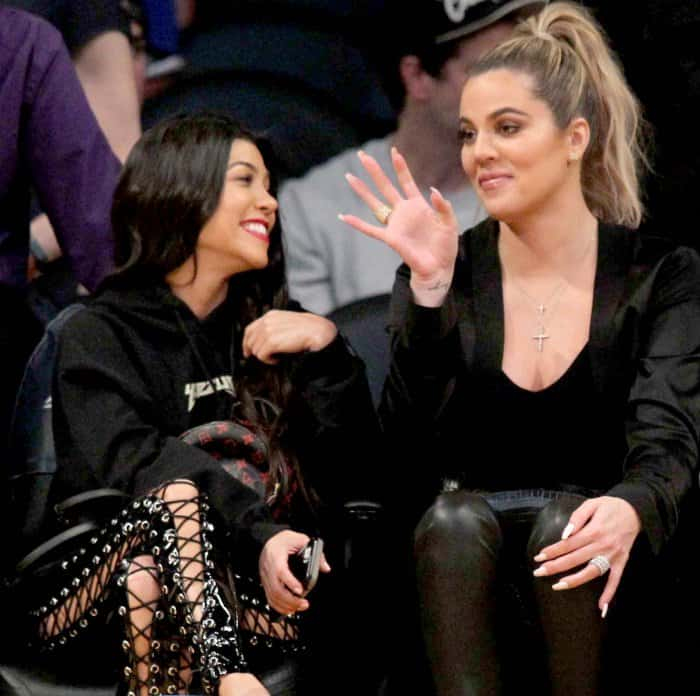 Kourtney Kardashian wearing Yeezy sandals and Khloe Kardashian wearing black pointy-toe pumps at Lakers vs. Cavaliers basketball game
