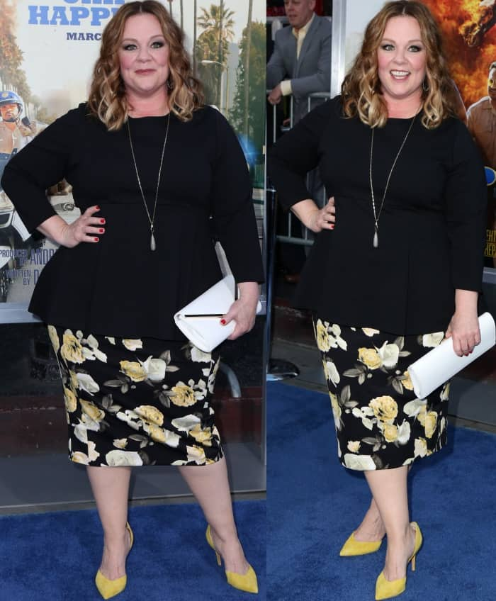 Melissa McCarthy wearing a Melissa McCarthy Seven7 flared peplum top, floral skirt, and yellow suede pumps