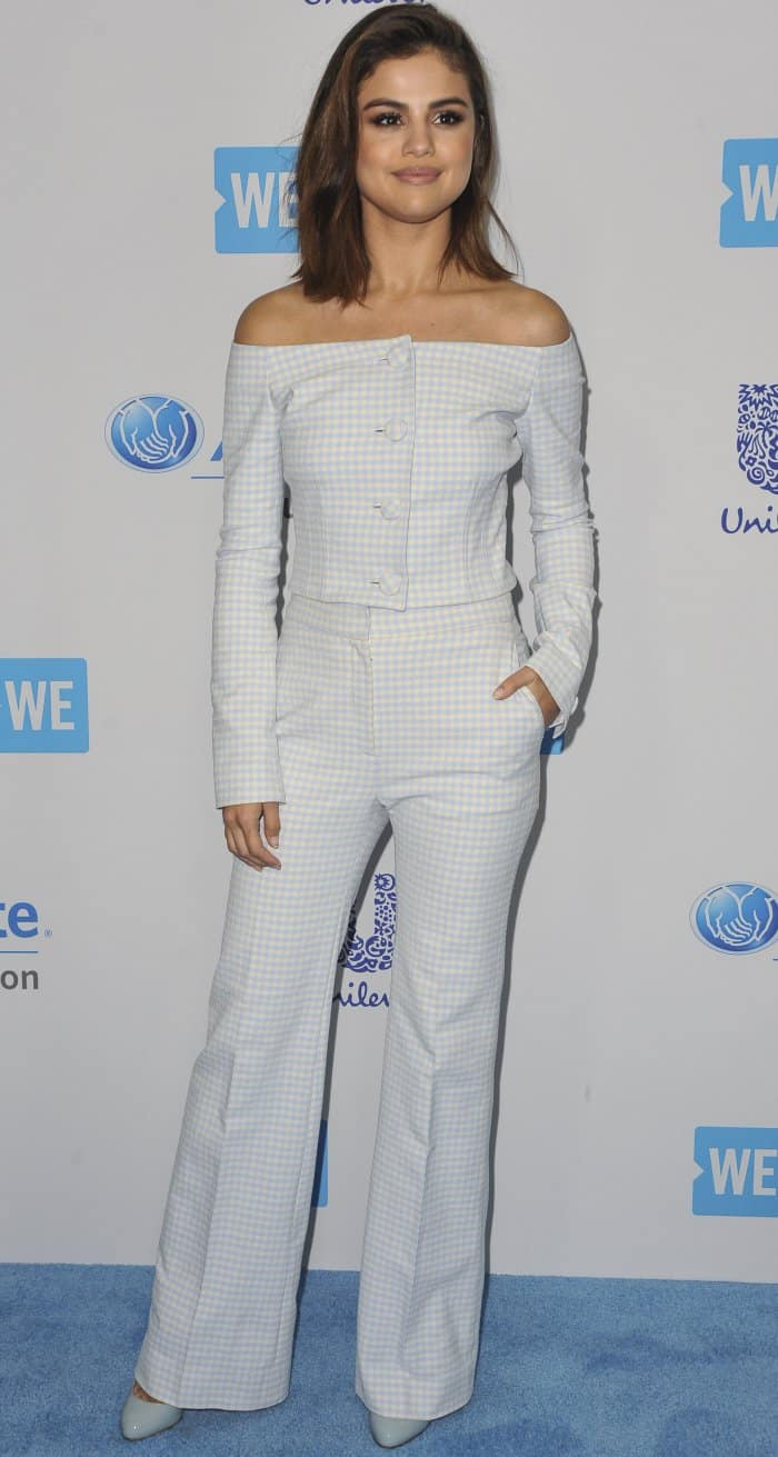 Selena Gomez in a pale blue off-the-shoulder button-up top with a gingham pattern and matching flared pants
