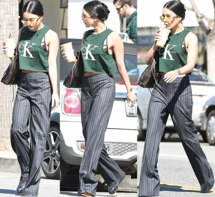 Vanessa Hudgens wearing a cropped Calvin Klein tank, striped pants, and Vince Camuto studded platform mules