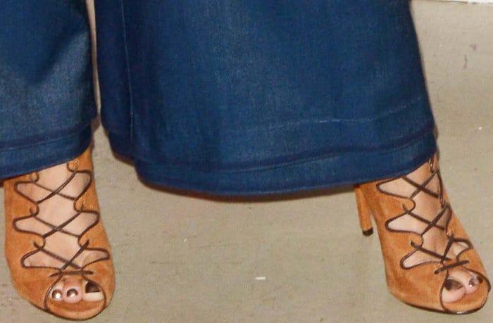 Vanessa Hudgens wearing a dark blue top, matching Manning Cartell pants, and Schutz lace-up sandals