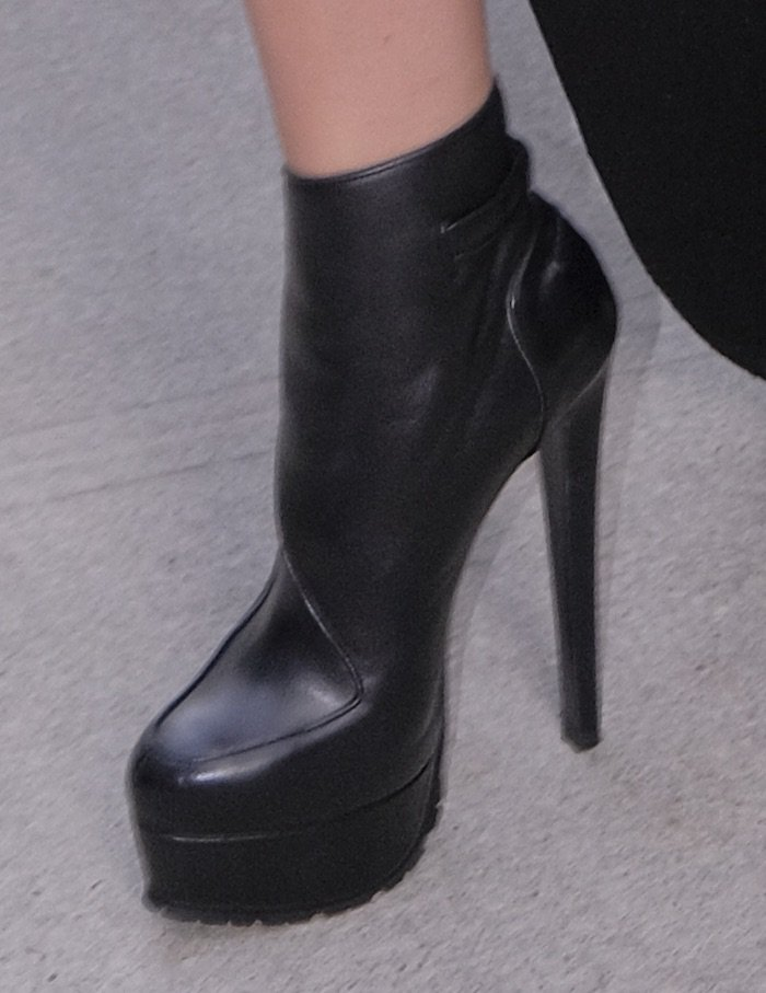 Hailee pairs her outfit with black leather platform boots also from Vera Wang