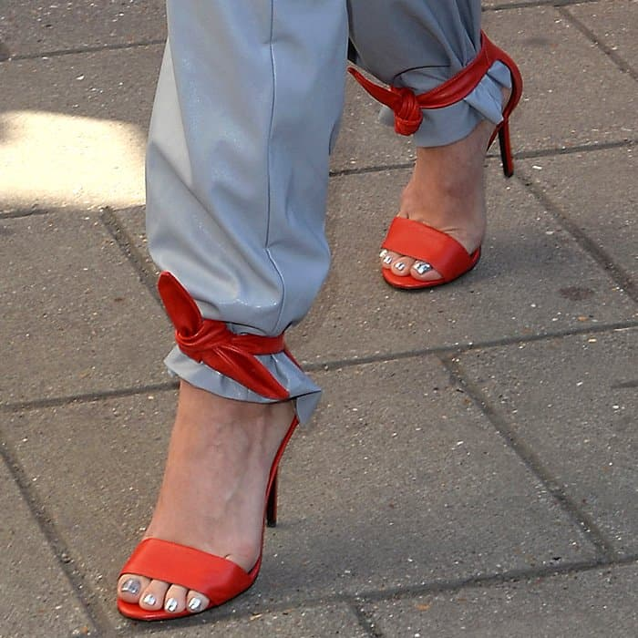 Closeups of Stella Luna red leather ankle-tie sandals on Katy Perry.