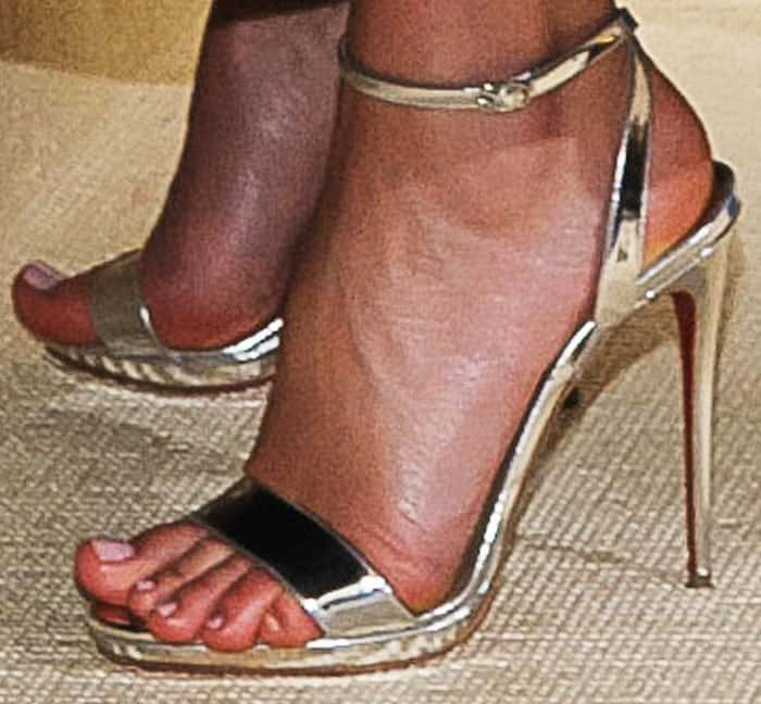 Miranda wears a pair of metallic sandals by Christian Louboutin