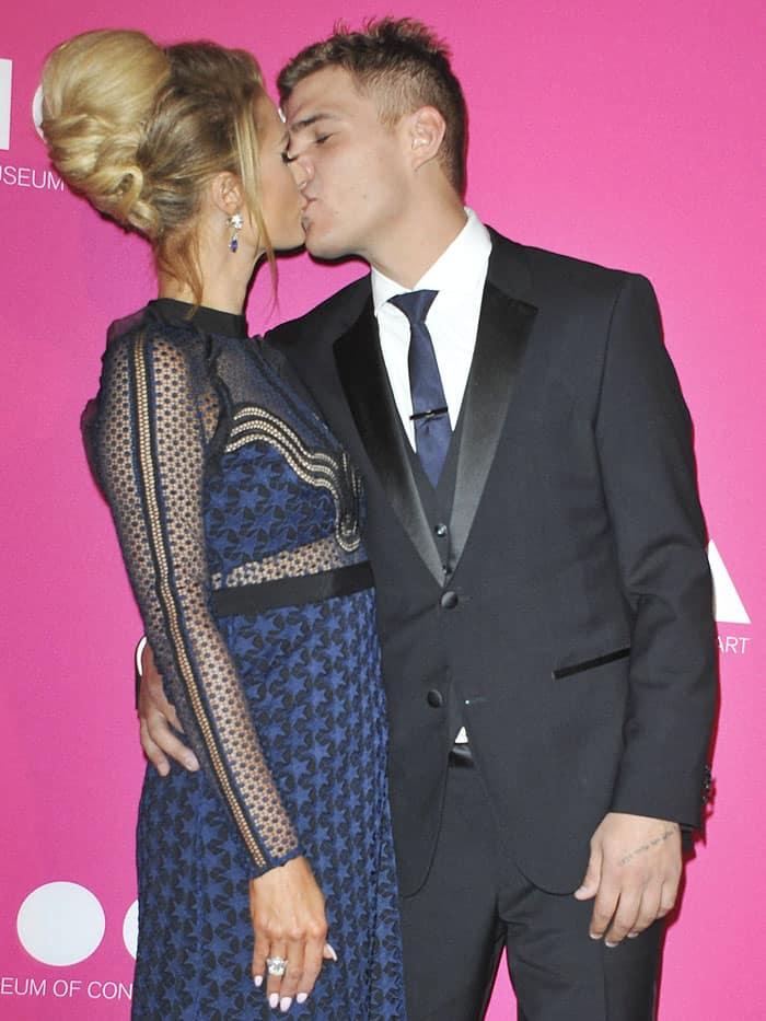 Paris Hilton sharing a kiss with boyfriend Chris Zylka on the purple carpet.