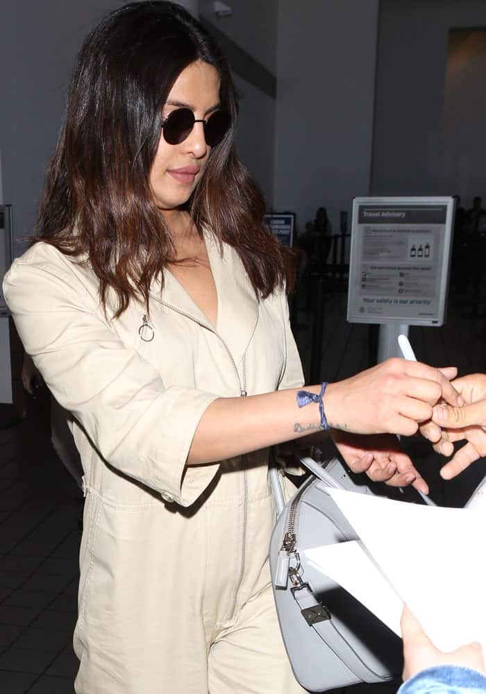 The actress stops to sign autographs for her airport fans