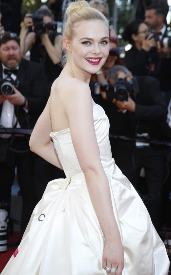 "Elle Fanning wearing a custom Vivienne Westwood ball gown and Christian Louboutin shoes at the 70th Cannes Film Festival ""Ismael's Ghosts"" premiere"